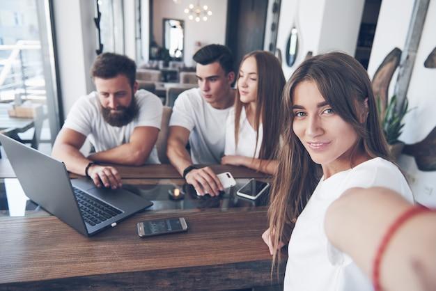 Um grupo de jovens com gadgets e um laptop organiza um brainstorm e se comunica entre si. o conceito de desenvolver uma empresa jovem.