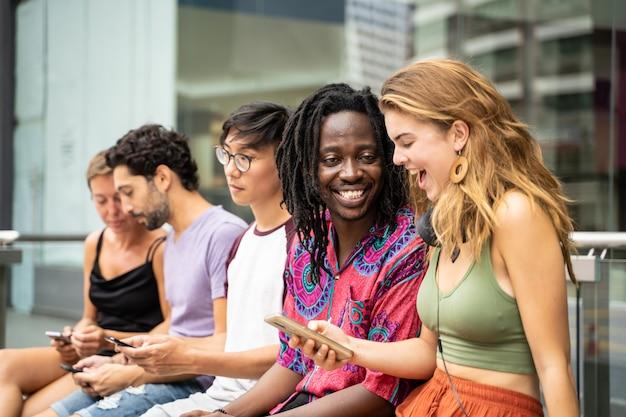 Um grupo de jovens de diferentes etnias sentado na rua com seus celulares nas mãos