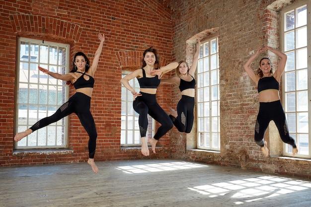 Um grupo de jovens desportivas congeladas em um salto, levitação.
