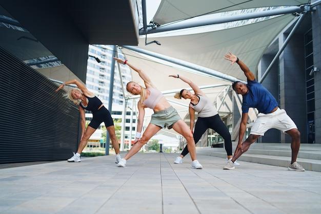 Um grupo de jovens e idosos fazendo exercício ao ar livre na cidade.