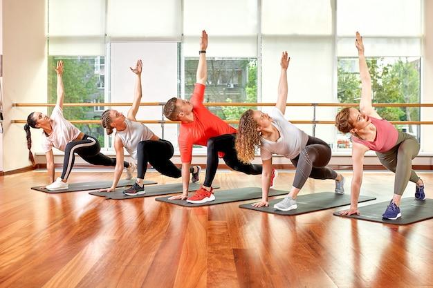 Um grupo de jovens esportivos em roupas esportivas, em uma sala de fitness, fazendo flexões ou pranchas na academia.