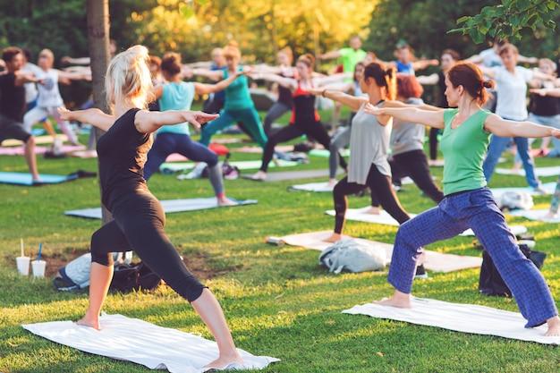 Um grupo de jovens faz yoga no parque ao pôr do sol.
