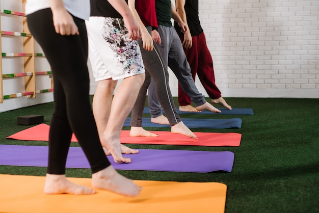 Um grupo de jovens fazendo exercícios joga dentro de casa na academia