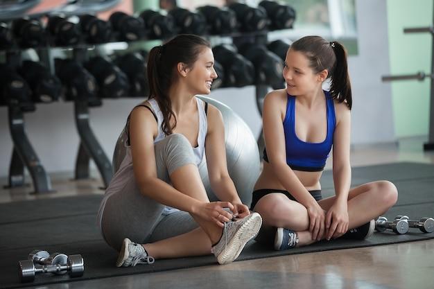 Um grupo de jovens garotas bonitas descansando após o treinamento no chão. belas garotas conversando na academia após treino de fitness