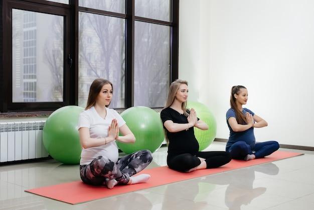 Um grupo de jovens grávidas pratica ioga e esportes em tapetes internos. estilo de vida saudável.
