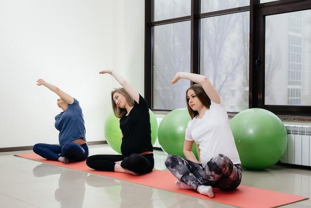 Um grupo de jovens grávidas pratica ioga e esportes em tapetes internos.