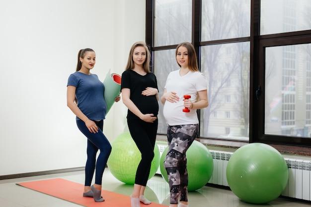 Um grupo de jovens grávidas pratica ioga e socializa dentro de casa. estilo de vida saudável