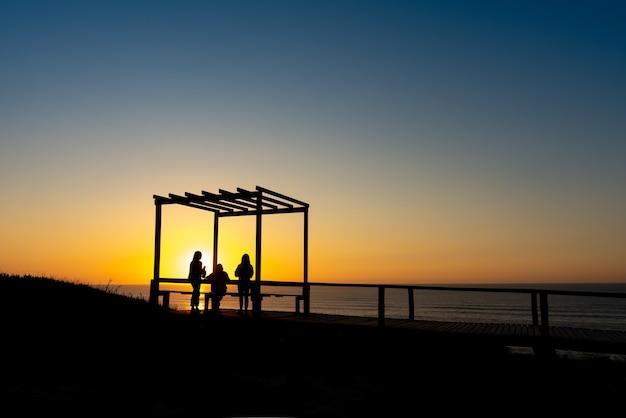 Um grupo de jovens num miradouro a ver o pôr do sol na praia portuguesa de são pedro de moel - portugal.