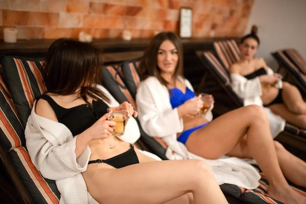 Um grupo de jovens relaxantes em um deck de madeira na sauna. se divertindo na companhia feminina