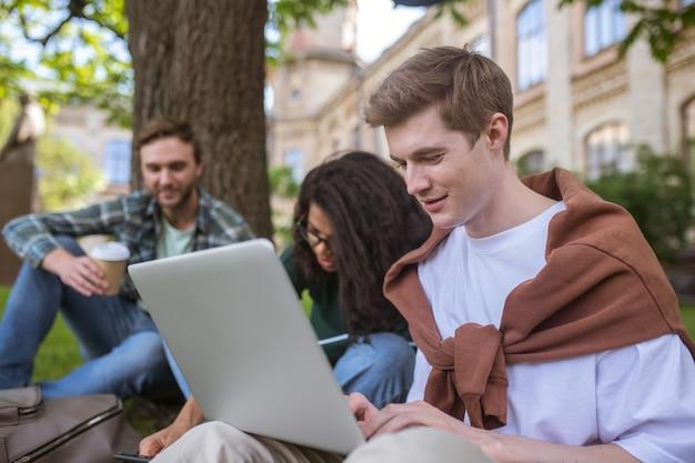 Um grupo de jovens sentados na grama se preparando para os exames