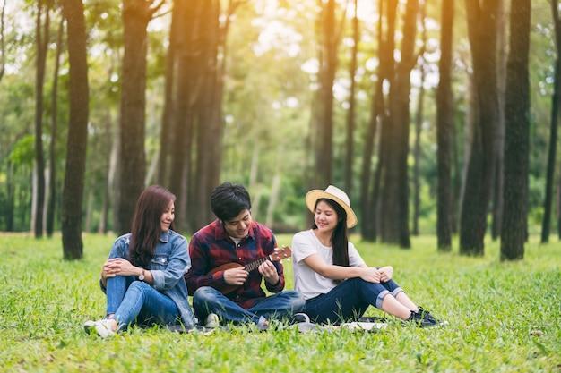 Um grupo de jovens tocando ukulele sentados no parque