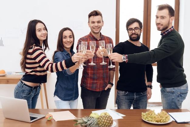 Um grupo de jovens trabalhadores de escritório comemorando.
