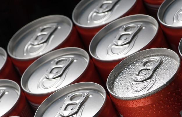 Um grupo de latas vermelhas com um close de gotas de água em um fundo preto Foto Premium