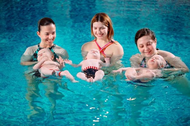 Um grupo de mães com seus filhos pequenos em uma aula de natação infantil com um treinador.