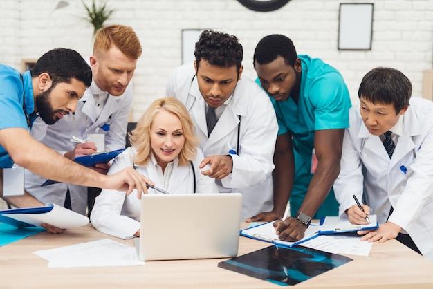 Um grupo de médicos olha para algo no laptop.