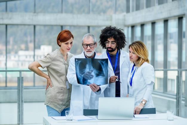 Um grupo de médicos olhando para um raio-x em uma conferência médica, discutindo questões.