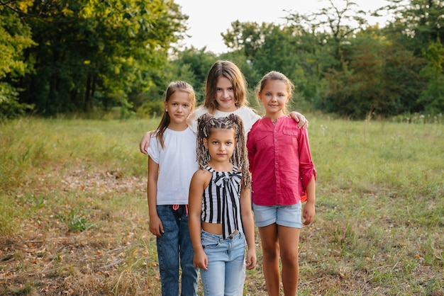 Um grupo de meninas alegres está sorrindo e brincando no parque durante o pôr do sol. acampamento de verão infantil.