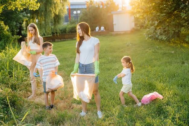 Um grupo de meninas com filhos ao pôr do sol está envolvido na coleta de lixo no parque. cuidado com o meio ambiente, reciclagem.