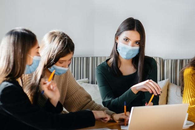 Um grupo de meninas mascaradas está sentado em um café e trabalha em laptops. alunos de ensino.
