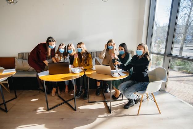 Um grupo de meninas mascaradas está sentado em um café e trabalhando em laptops