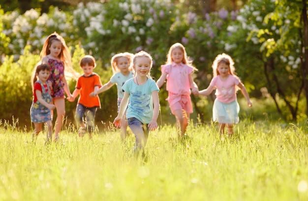 Um grupo de meninos e meninas crianças felizes correndo no parque na grama em um dia ensolarado de verão.