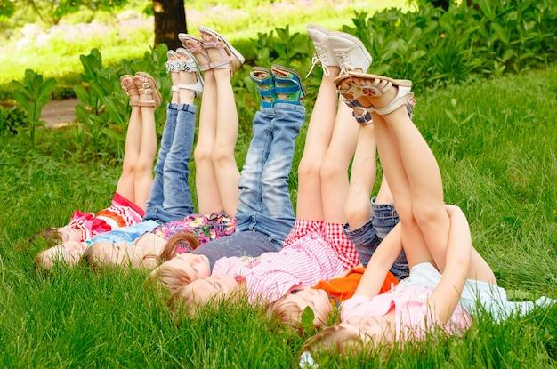 Um grupo de meninos e meninas crianças felizes, deitado no parque na grama em um dia ensolarado de verão.
