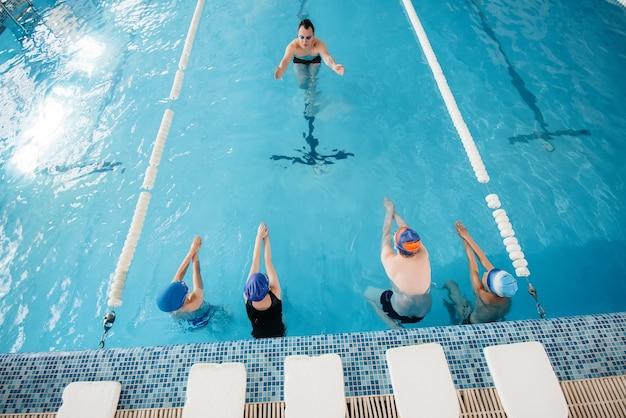 Um grupo de meninos e meninas treina e aprende a nadar na piscina com um instrutor. desenvolvimento de esportes infantis. Foto Premium