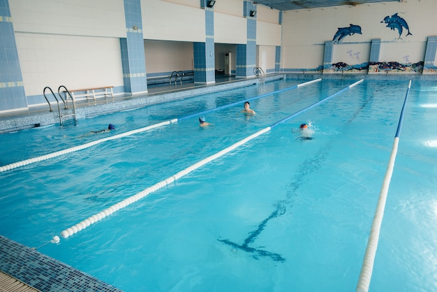 Um grupo de meninos e meninas treina e aprende a nadar na piscina com um instrutor