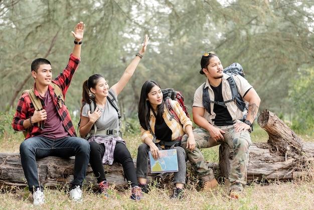 Um grupo de mochileiros asiáticos, homens e mulheres, olhou e ergueu as mãos, convidando aqueles que haviam se reunido para sentar nas toras da floresta.