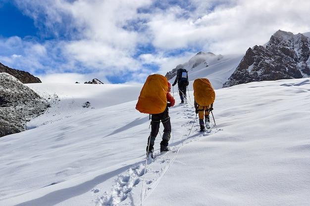 Um grupo de montanhistas sobe ao topo de uma montanha coberta de neve