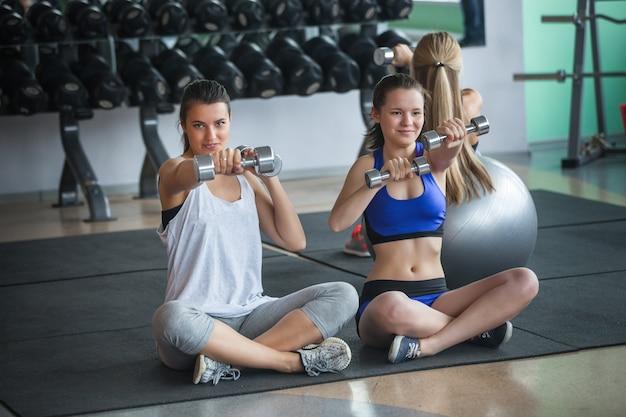 Um grupo de mulheres atraentes treinando na academia com halteres. jovens garotas bonitas têm um treino no ginásio