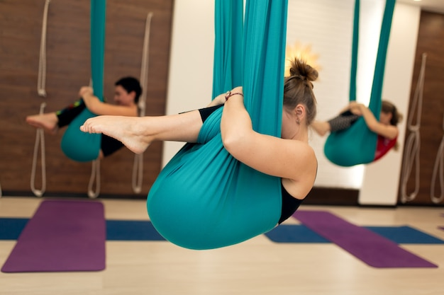 Um grupo de mulheres está pendurado em uma posição fetal em uma rede. voar aula de ioga no ginásio