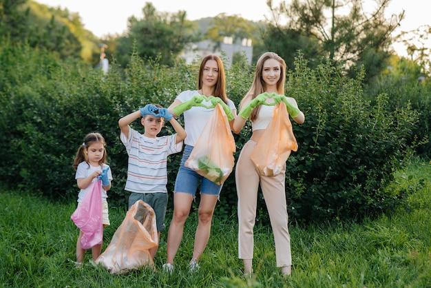 Um grupo de mulheres jovens com filhos mostra corações após limpar o lixo do parque durante o pôr do sol. cuidado com o meio ambiente, reciclagem.