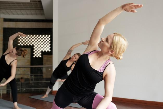 Um grupo de mulheres praticando ioga, estendendo-se para o lado