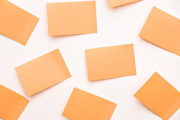 Um grupo de notas de post-it cor de laranja, papel autocolante e blocos de notas na parede
