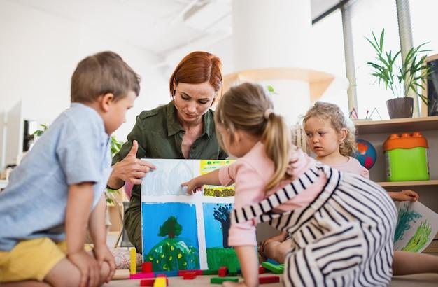 Um grupo de pequenas crianças da creche com o professor no chão dentro de casa na sala de aula, aprendendo.