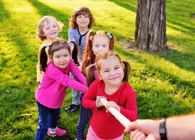 Um grupo de pequenas crianças pré-escolares joga um cabo de guerra no parque.