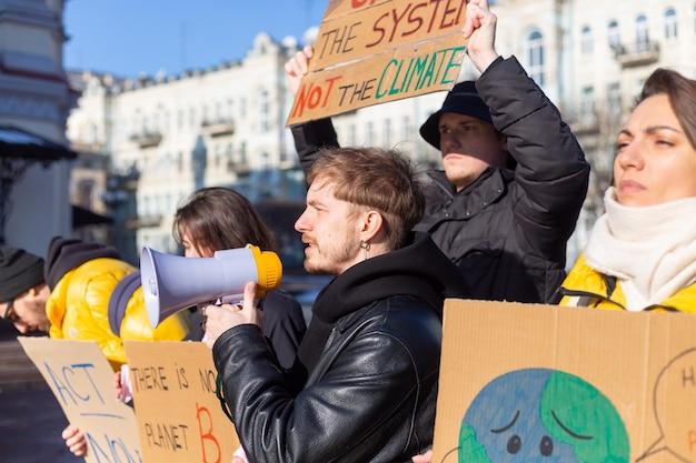 Um grupo de pessoas com faixas e um megafone na mão protestam na praça da cidade por svae planet clean world act now
