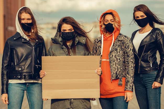 Um grupo de pessoas com máscara e cartazes para protestar o protesto da população contra o coronavírus e contra a introdução de quarentena