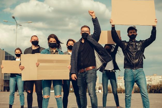 Um grupo de pessoas com máscara e cartazes para protestar o protesto da população contra o coronavírus