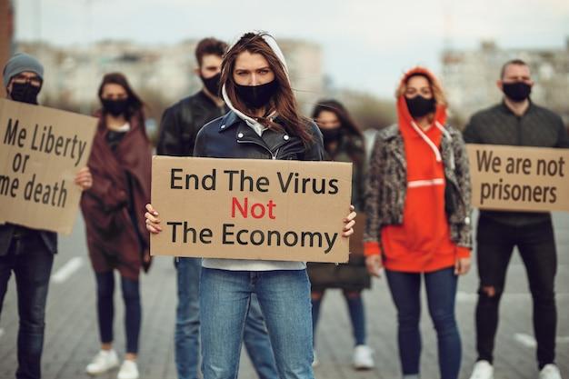 Um grupo de pessoas com máscara e cartazes