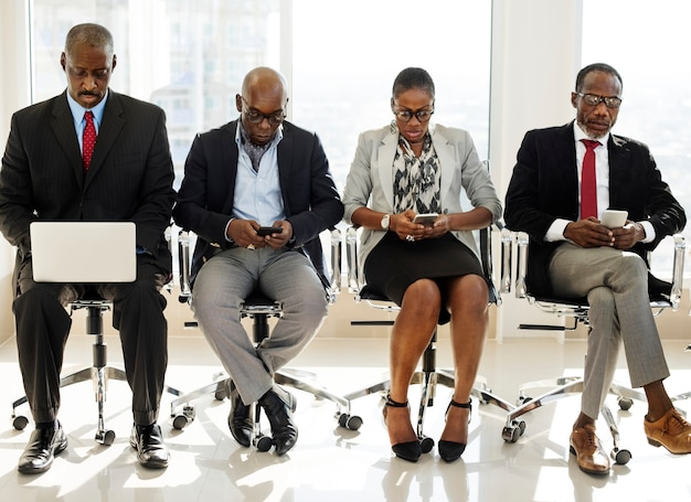 Um grupo de pessoas de negócios internacionais está sentado e usando dispositivos sem fio