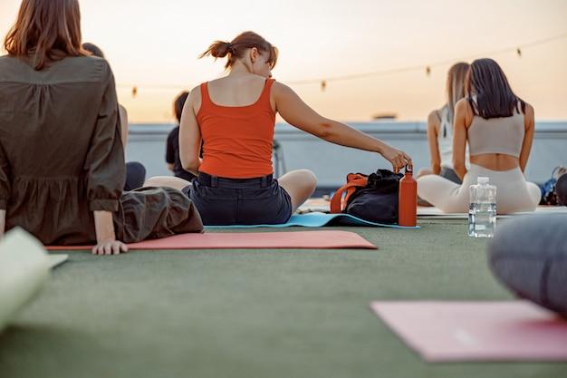 Um grupo de pessoas diferentes está fazendo práticas de ioga meditativa no telhado em um belo pôr do sol na noite de verão