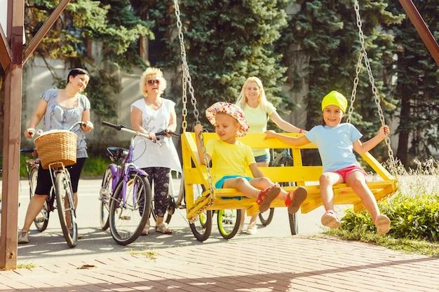 Um grupo de pessoas é uma grande família de 5 pessoas em pé posando de bicicleta em um parque da cidade em uma estrada em um dia ensolarado