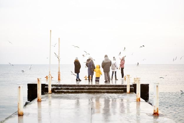 Um grupo de pessoas em roupas de inverno estão de pé no banco dos réus e alimentando as gaivotas de suas mãos.