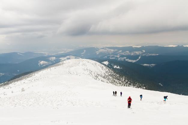 Um grupo de pessoas em um planalto sobe até o topo da montanha