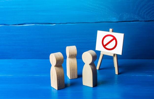 Um grupo de pessoas está olhando para um cavalete com um símbolo proibitivo vermelho não