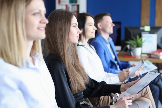 Um grupo de pessoas está sentado na poltrona com documentos nas mãos e ouvindo a palestra