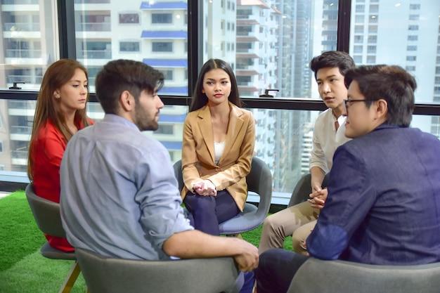 Um grupo de pessoas está trabalhando em conjunto para discutir problemas de saúde mental na forma de saúde mental, estresse no trabalho.