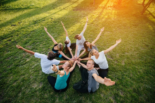 Um grupo de pessoas faz ioga em um círculo ao ar livre durante o pôr do sol. estilo de vida saudável, meditação e bem-estar.